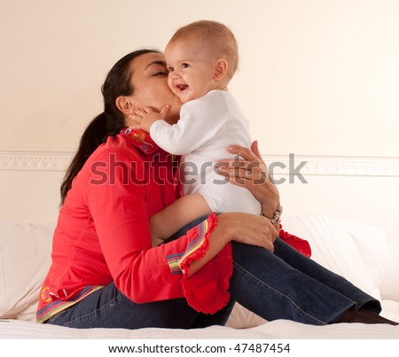 Woman sitting on a bed kissing her baby - stock photo