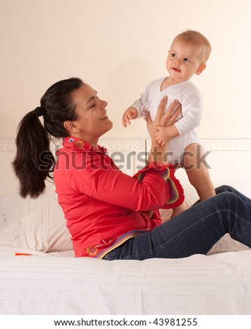 Woman sitting on a bed lovingly holding her baby - stock photo