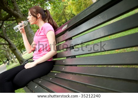 Woman sitting on a bench outdoors drinking water - stock photo
