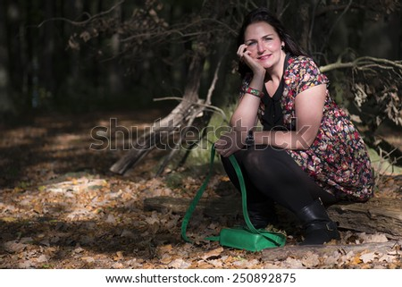 woman sitting on a branch in a forrest - stock photo