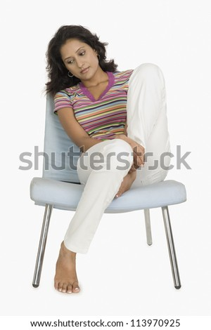 Woman sitting on a chair and looking serious - stock photo