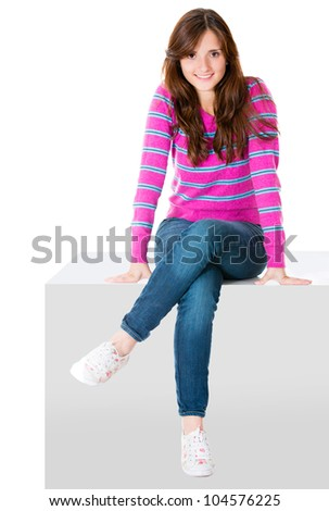 Woman sitting on a cube - isolated over a white background - stock photo