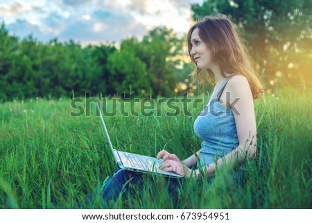 Woman sitting on a green meadow with trees on the background of sunset with clouds. Working or studying on laptop wireless. The concept of education with nature