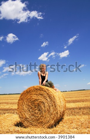 Woman sitting on a hay bale in summer stubble field under a bright vivid sky