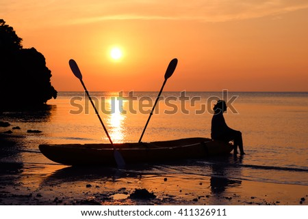 Woman sitting on a kayak on the beach at sunset.