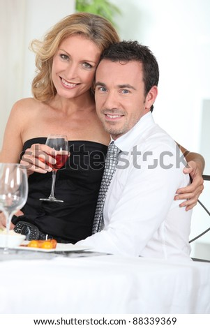 Woman sitting on a man's lap at the dinner table - stock photo