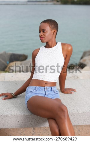 Woman sitting on a park bench and looking away - stock photo
