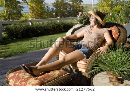 Woman sitting on a patio chair relaxing at home by the lake - stock photo