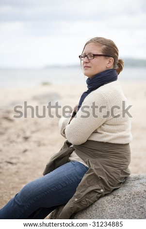 Woman sitting on a rock with a thoughtful expression - stock photo