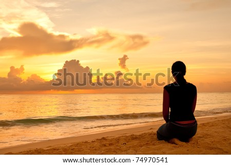 Woman sitting on a sand beach in front of sunset and ocean in summer