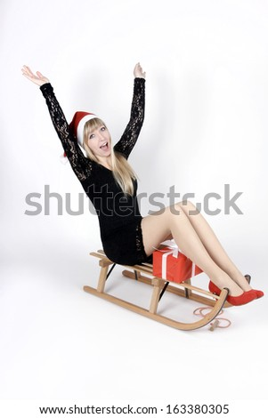 Woman sitting on a sleigh holding a christmas gift - stock photo