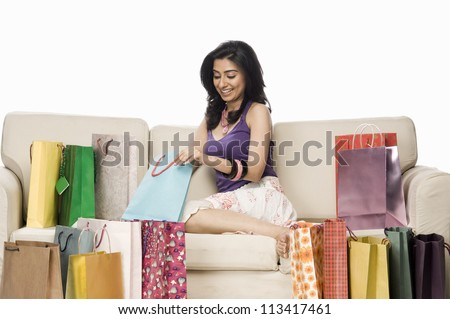 Woman sitting on a sofa and holding a shopping bag - stock photo