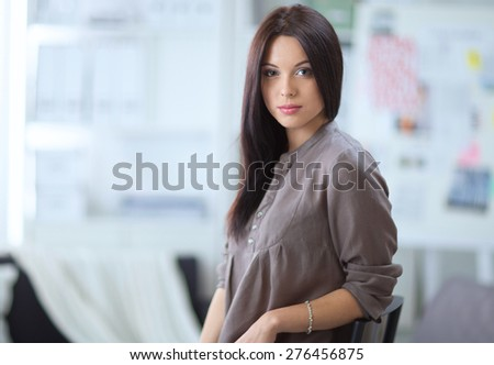 Woman sitting on a sofa in her house with camera - stock photo