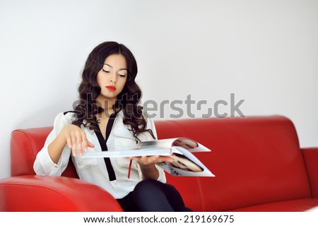 Woman sitting on a sofa while holding a magazine in a living room - stock photo