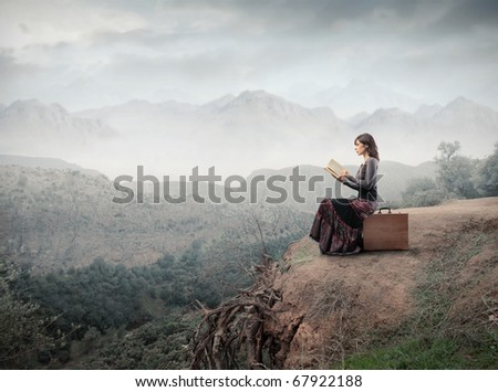 Woman sitting on a suitcase and reading a book with landscape on the background - stock photo