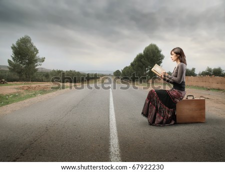 Woman sitting on a suitcase on a countryside road and reading a book - stock photo