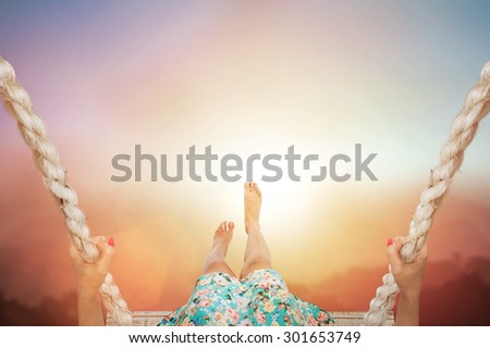 Woman sitting on a swing with abstract pastel forest blurred background.freedom concept - stock photo
