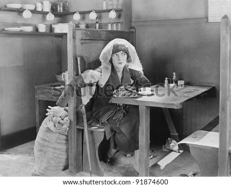 Woman sitting on a vanity smelling perfume