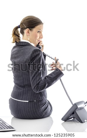 Woman sitting on a white office desk talking on a telephone.