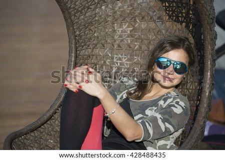 Woman sitting on a wicker swing outdoor. Woman in glasses riding in a wicker chair suspended in the park sunny summer day. - stock photo