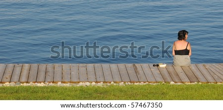 Woman sitting on a wooden dock