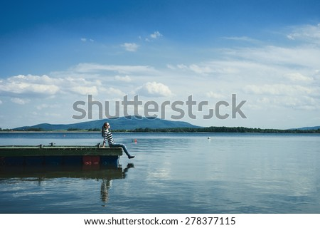 Woman sitting on a wooden jetty enjoying the sunshine. - stock photo