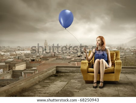 Woman sitting on an armchair  and holding a balloon with landscaped on the background - stock photo