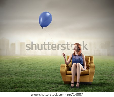 Woman sitting on an armchair on a green meadow and holding a balloon with cityscape on the background - stock photo