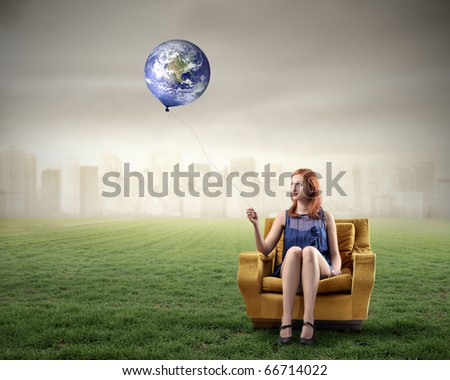 Woman sitting on an armchair on a green meadow and holding the Earth like a balloon with cityscape on the background - stock photo