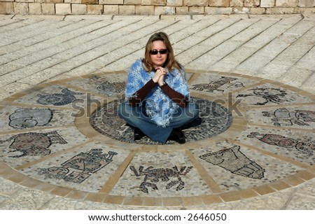 Woman sitting on antic astrological wheel - stock photo