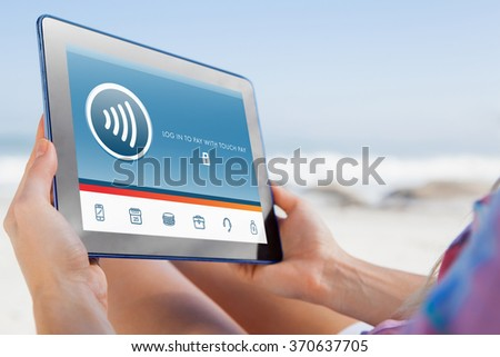 Woman sitting on beach in deck chair using tablet pc against web - stock photo