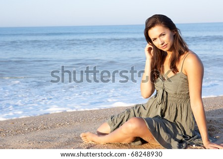 Woman sitting on beach relaxing - stock photo