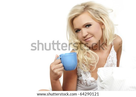 Woman sitting on bed drinking coffee smiling