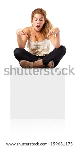 Woman sitting on blank empty box, pointing down at copy space. - stock photo