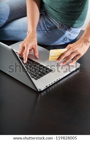 woman sitting on brown table typing on laptop - stock photo