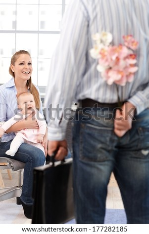 Woman sitting on chair with little daughter on lap, smiling happy at husband arriving home from work with flower hidden behind back.