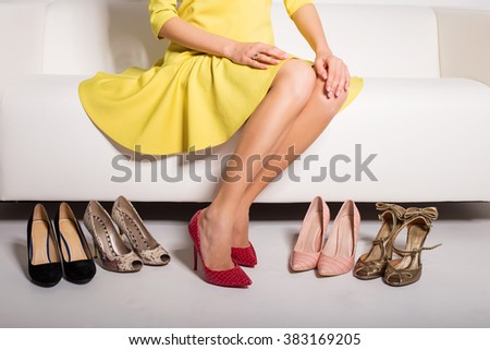 Woman sitting on couch  and choosing what shoes to wear  - stock photo