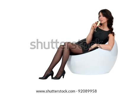 Woman sitting on couch with a glass of champagne - stock photo
