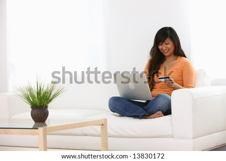 Woman sitting on couch with laptop and credit card