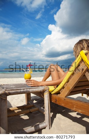 Woman sitting on deckchair and enjoying a cocktail on a tropical beach - stock photo
