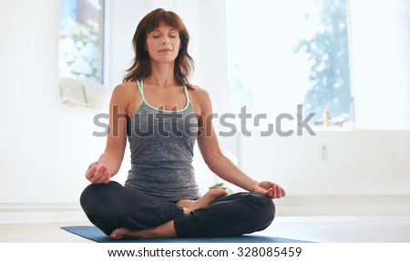 Woman sitting on exercise mat in lotus position with her eyes closed doing yoga. Fit caucasian female practicing Padmasana at gym. - stock photo
