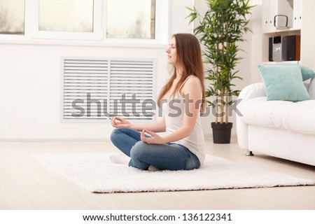 Woman sitting on floor at home doing yoga meditation - stock photo