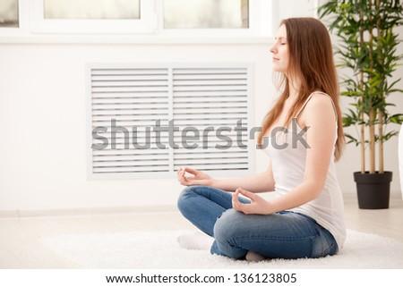 Woman sitting on floor at home doing yoga meditation - stock photo