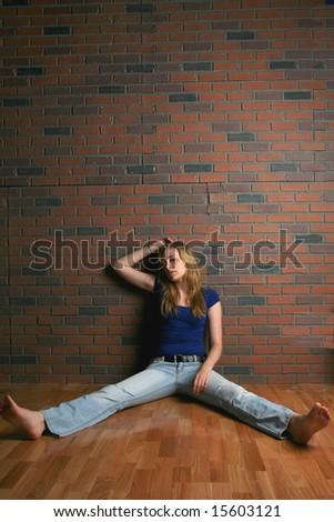woman sitting on floor near brick wall looking hopeless - stock photo