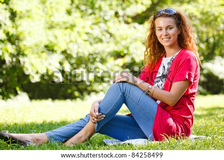 Woman sitting on grass in park - stock photo