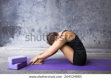 Woman sitting on her mat hiding her face between her legs. Finding refuge in yoga practice.  - stock photo