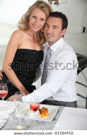 Woman sitting on her partner's lap at a dinner party - stock photo