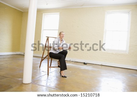 Woman sitting on ladder in empty space holding paper smiling - stock photo