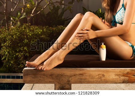 Woman sitting on lounge and moisturizing her skin - stock photo