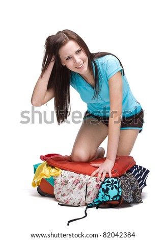 Woman sitting on luggage to close it. Isolated on white. - stock photo